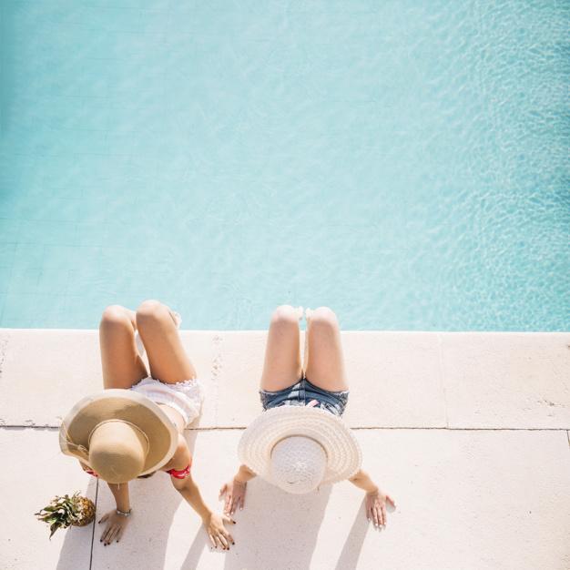 vue-de-dessus-des-filles-en-face-de-la-piscine_23-2147814780